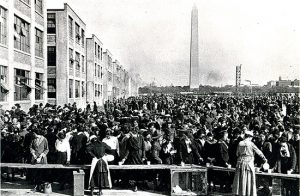 A crowd of people with the Washington Monument in the distance.