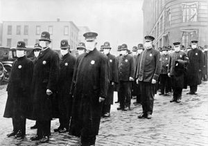Policemen patrol the streets in masks in Seattle to ensure public safety.