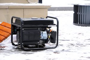 A portable generator sitting outside in the snow.