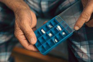 The hands of an elderly man holding a pill organizer