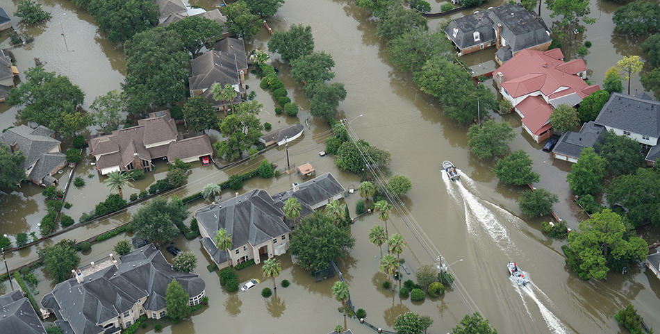 Two boats motor down a flooded residential street after Hurricane Harvey.