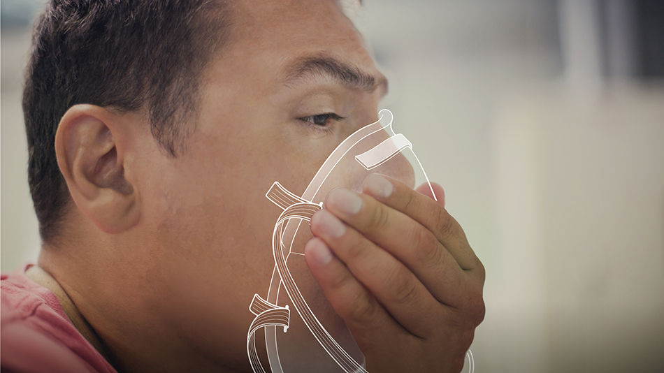 Close-up photo of a man putting on a respirator.