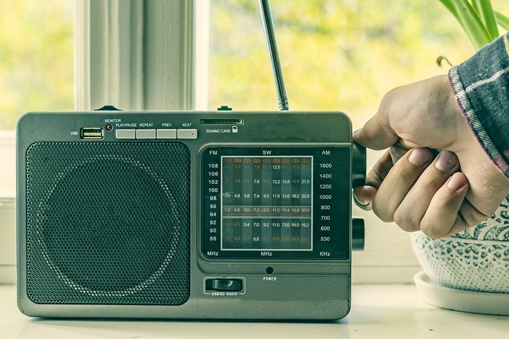Hand turning knob on vintage radio