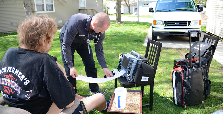A male paramedic performs a health check outside on a man sitting in a chair.