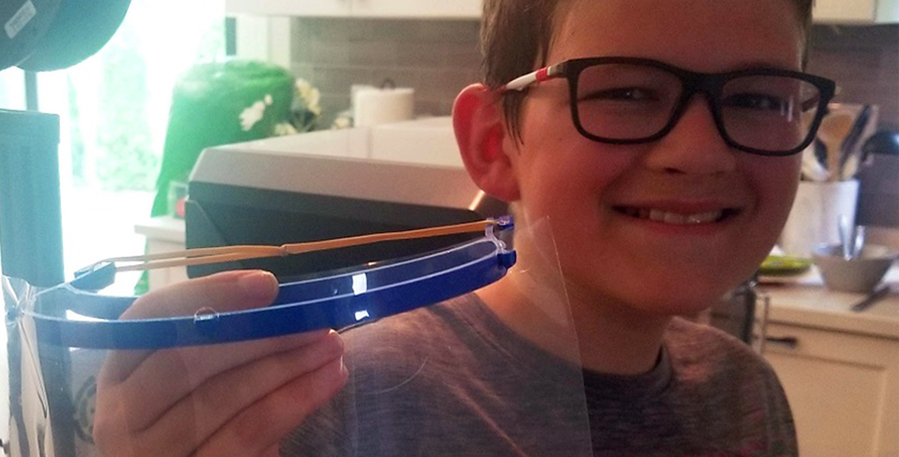 Boy holds up a face shield he made on a 3D printer