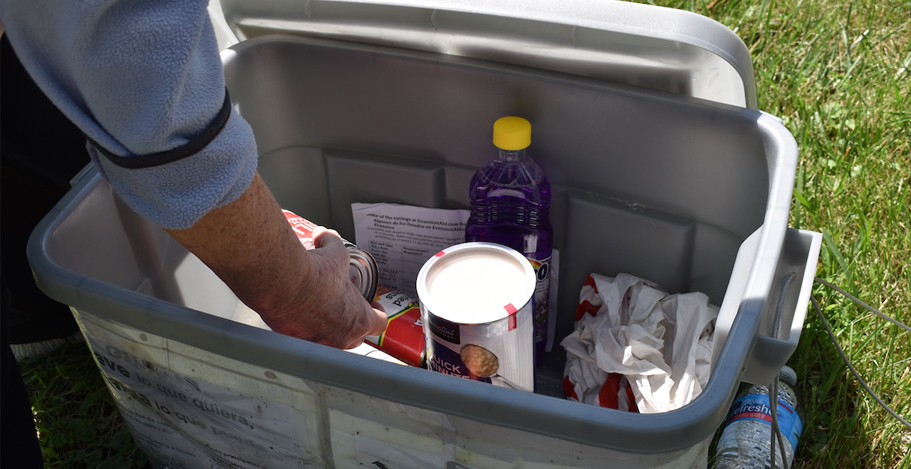 A person reaches into a plastic bin filled with nonperishable food and other supplies