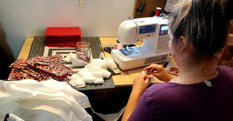 A woman uses a sewing machine to make masks.