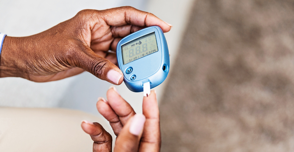 A woman tests her blood sugar using a blood glucose meter.