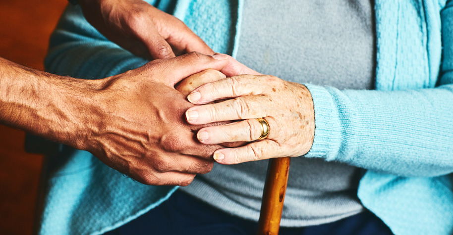A male caregiver holds the hand of an older woman.
