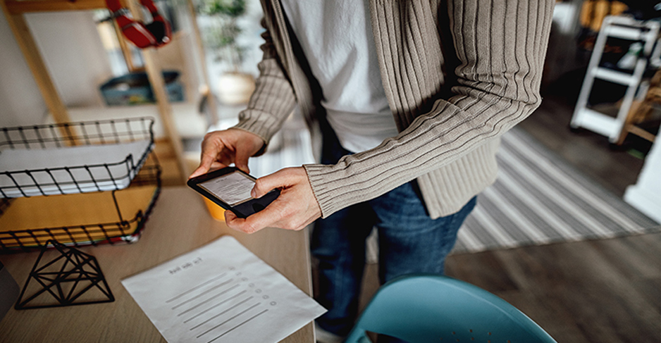 A person uses their smartphone to take a photo of a paper document.