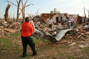 Photo of person in the foreground of residential tornado destruction